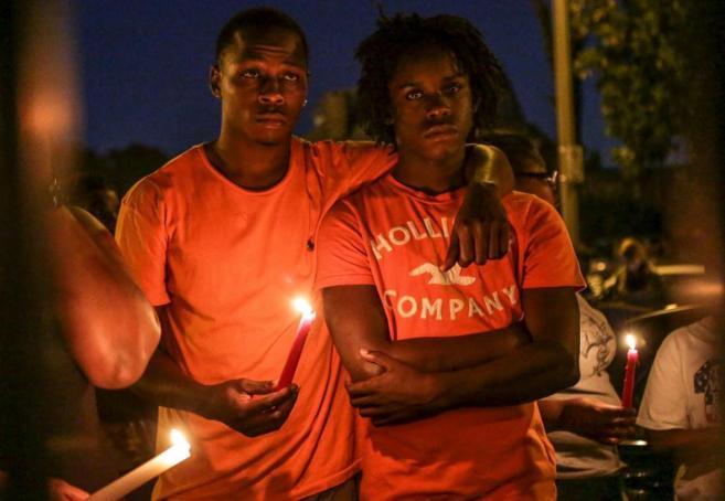 Familiares de Ball-Bey sostienen una vela en la vigilia del joven...