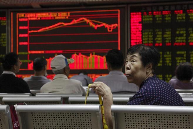 Varios inversores chinos observan la evolución de la bolsa en Pekín.