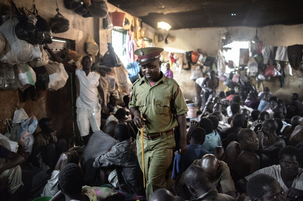Un vigilante de la prisión inspecciona una celda llena de inmigrantes...