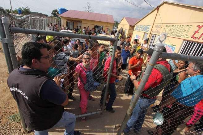 Funcionarios de migración venezolanos comprueban los documentos de...