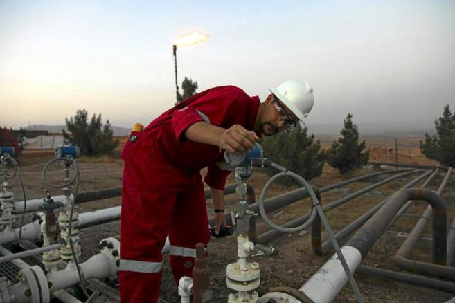 Un trabajador ajusta las válvulas de un yacimiento depetróleo