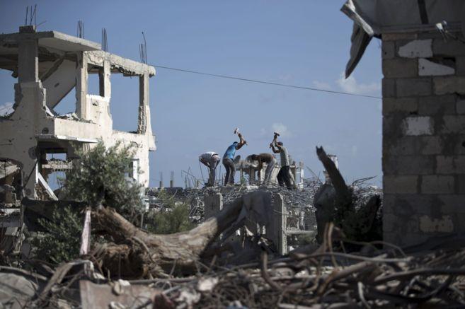 Varios palestinos intentar reconstruir un edificio en Gaza en el...