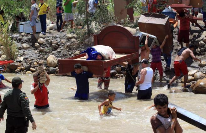 Cientos de colombianos cargan sus pertenencias desde Venezuela hacia...