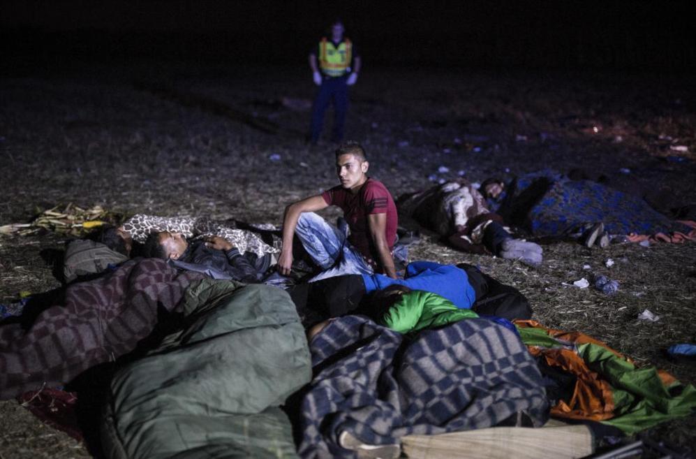 Varios ciudadanos sirios esperan a ser conducidos por la policía...
