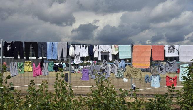 arias prendas tendidas en una valla en un campamento de recepción de...
