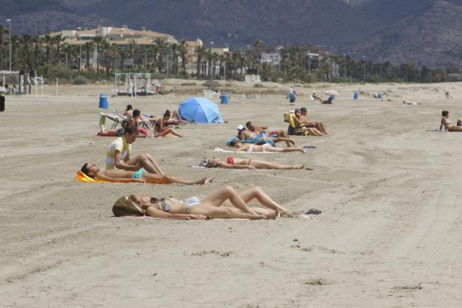 Gente tomando el sol en la playa del Grao.