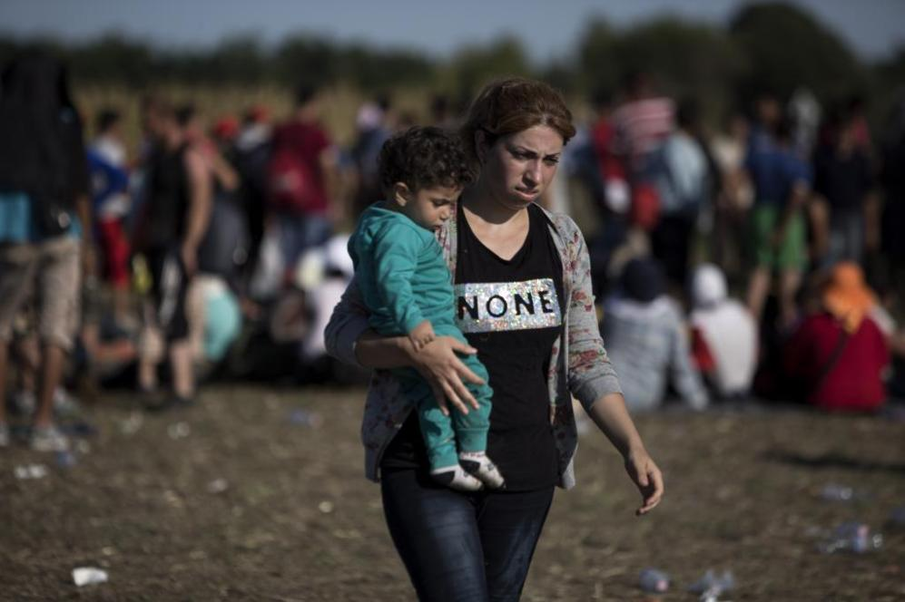 Una madre y su hijo, en una explanada tras la frontera, desde donde la...