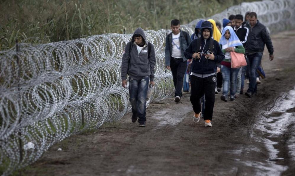 Un grupo camina junto a la valla en la localidad de Roszke.
