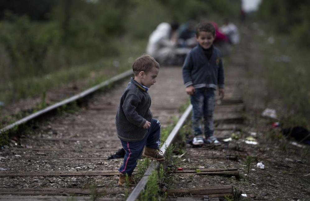 Unos niños juegan por las vías que comunican los dos países.