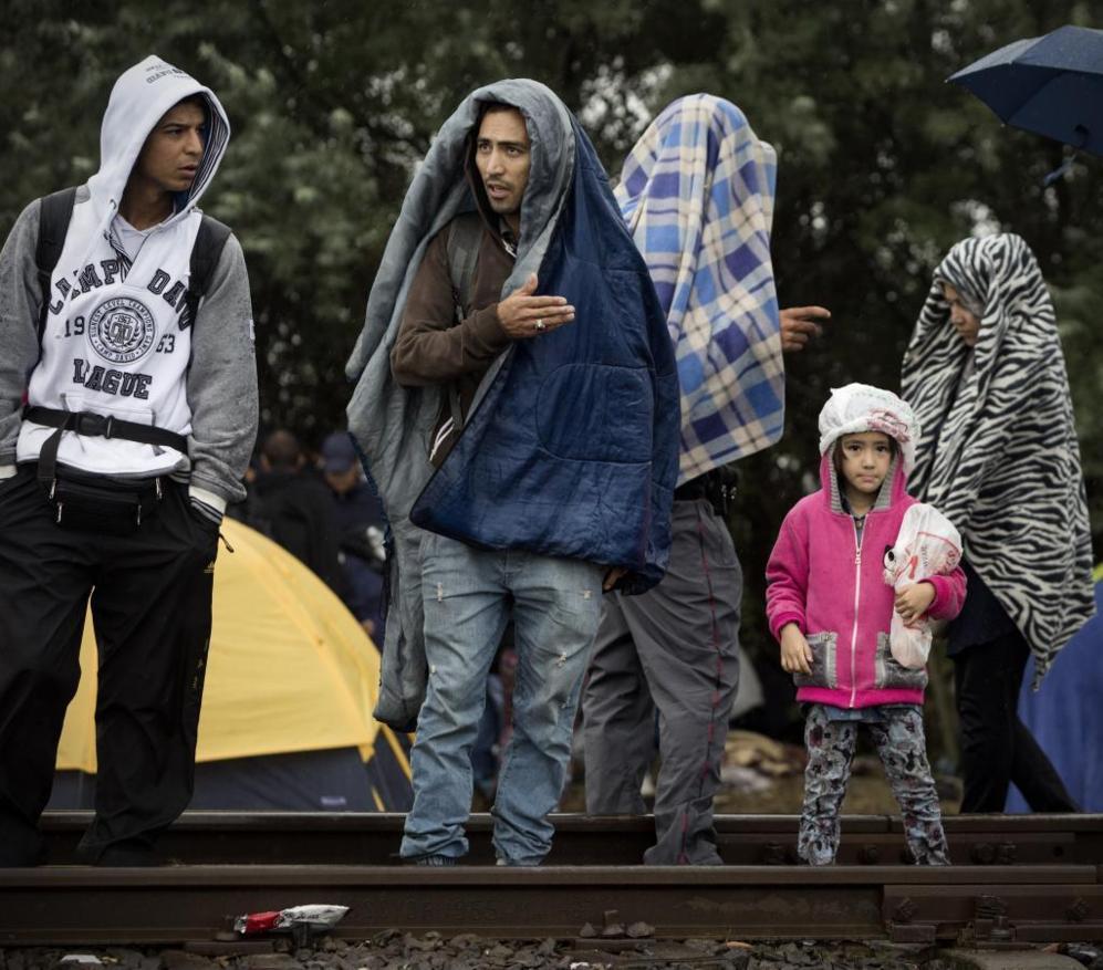 Una familia espera en las vías para cruzar la frontera...
