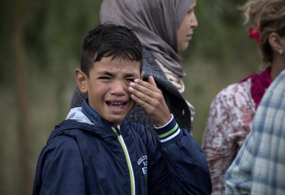 Un niño sirio llora tras ser detenida su familia por la policía en...