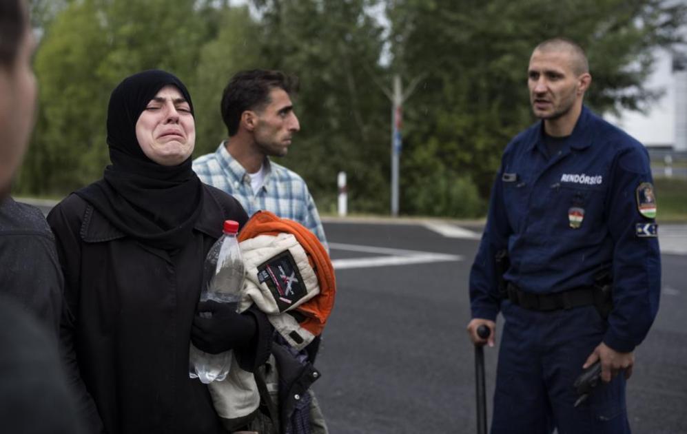 Una mujer siria llora tras ser detenida su familia por la policía en...