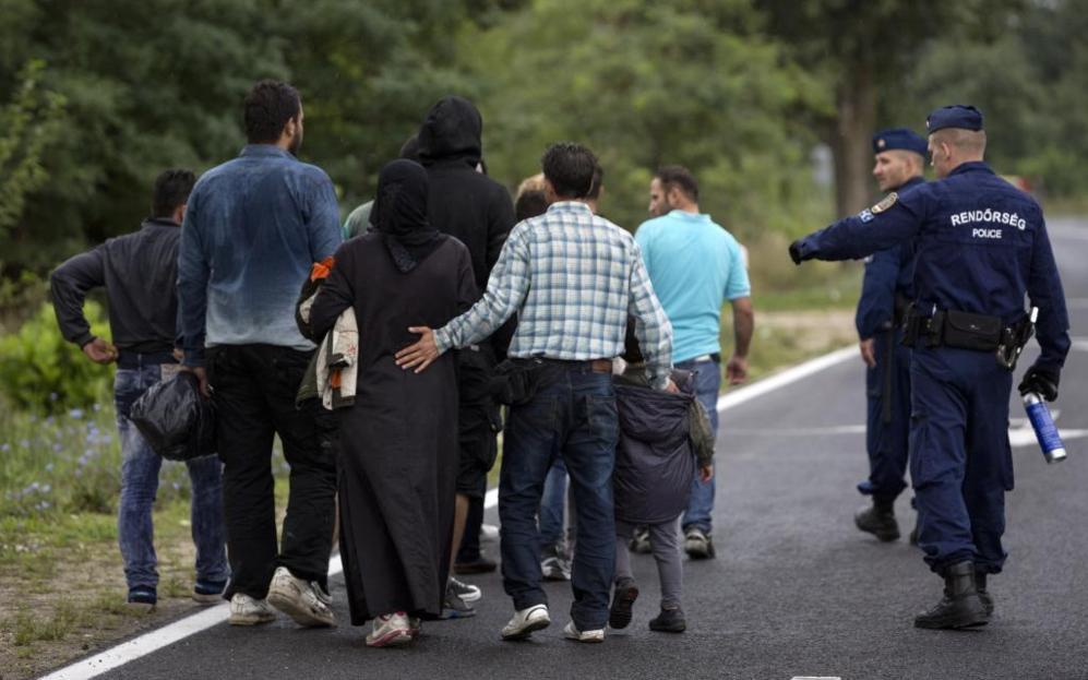Policías húngaros guían a una familia hacia el campo de refugiados...