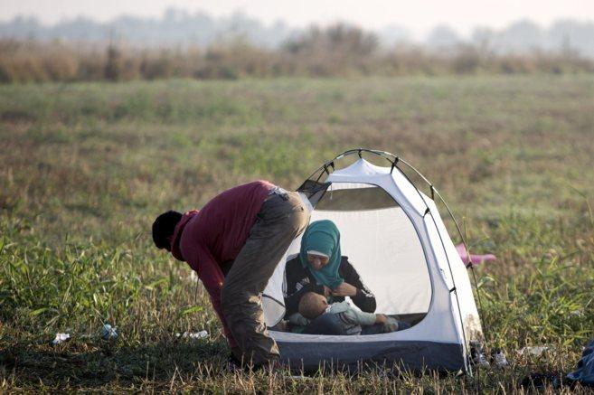 Una madre amamanta a su bebe junto a su marido.