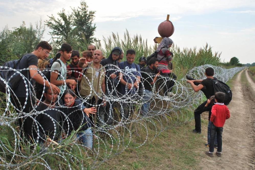 Varios refugiados sirios intentan saltar la alambrada de la frontera...