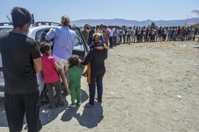 Varios inmigrantes hacen cola para recibir comida en la isla de Kos,...