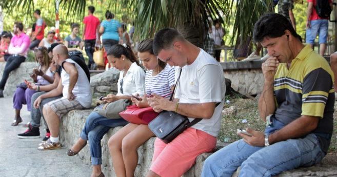 Varias personas revisando el celular durante su coneccion con Wifi, en...