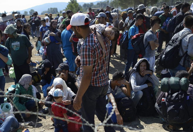 Inmigrantes esperan en el paso fronterizo de Macedonia y Grecia cerca...