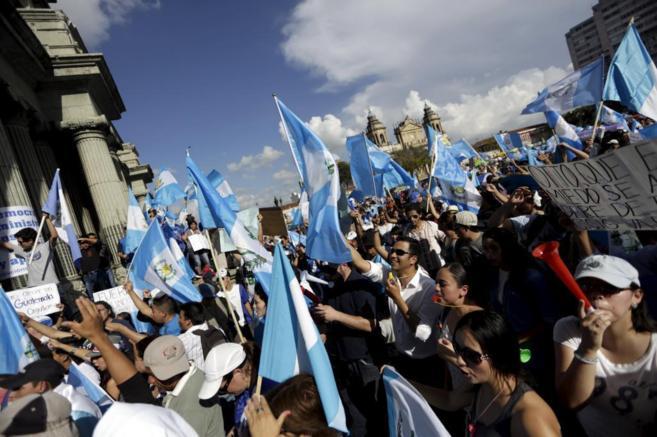 Guatemaltecos ondean banderas del país en la última manifestación...