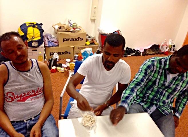 Dos refugiados eritreos y un migrante nigeriano esperan con sus...