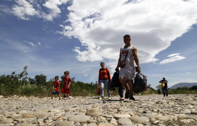 Familias colombianas cruzan desde Venezuela hacia Colombia a través...