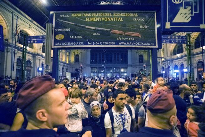 Inmigrantes esperan en una estación de Hungría para subir al tren...
