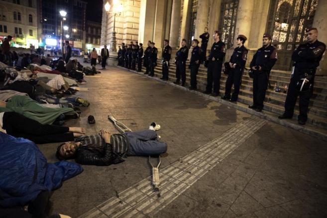 Un grupo de refugiados duerme a la intemperie a las puertas de la...