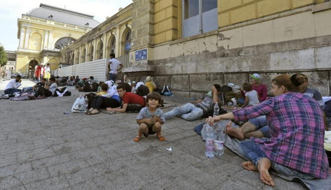 Un grupo de refugiados descansan en el exterior de la estación de...