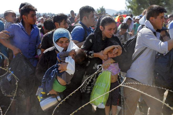 Migrantes cruzan la frontera entre Macedonia y Grecia cerca de...