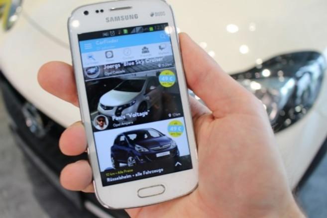Un conductor sujeta un teléfono móvil delante de su vehículo