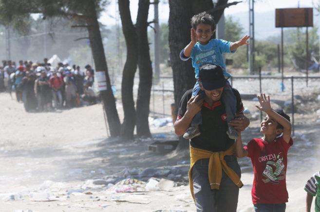 Un grupo de refugiados a la espera de cruzar la frontera entre...