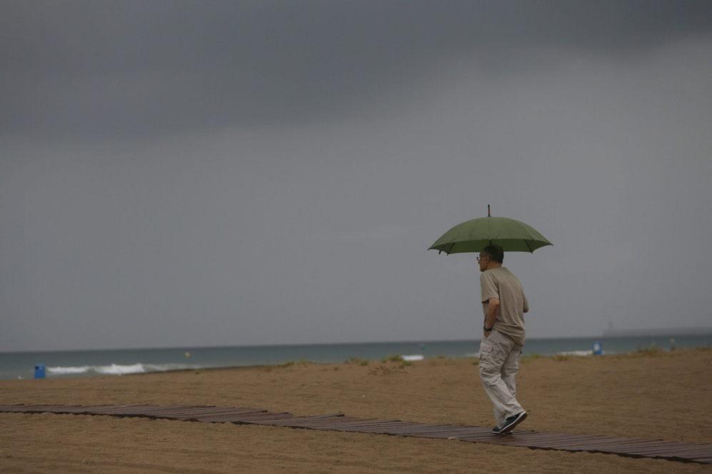 Un hombre pasea bajo la lluvia en la playa de la Malvarrosa (Valencia)...