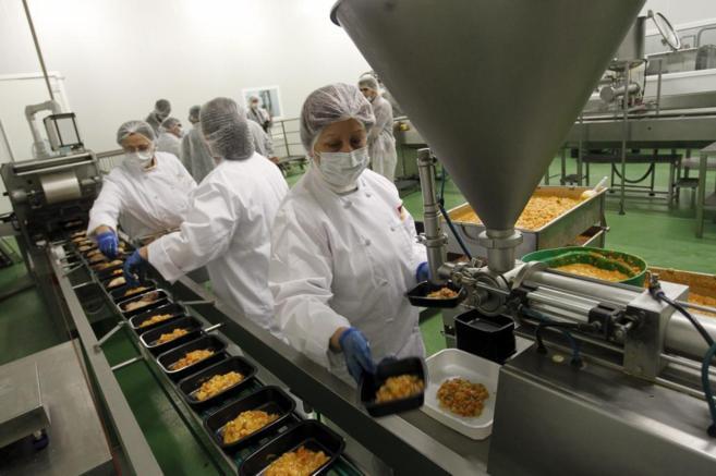 Un grupo de trabajadores empaquetando comida para entregarla a...