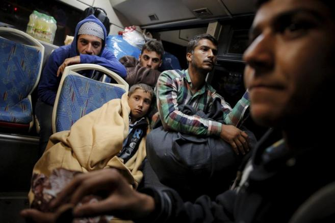 Varios refugiados en los autobuses del traslado.