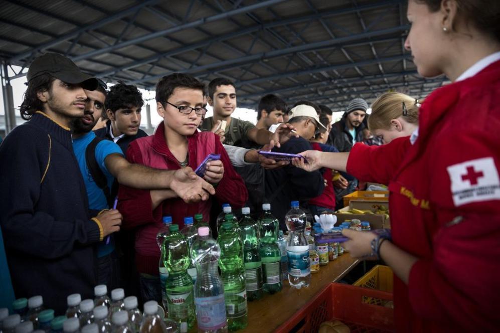 Varios jóvenes recogen comida en el puesto de la Cruz Roja habilitado...