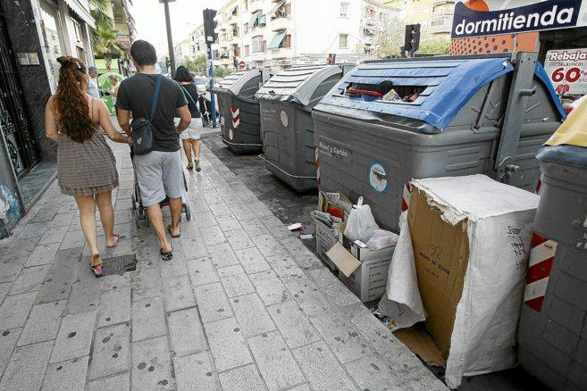 Contenedores repletos de basura y suciedad que llega a la calle por la...