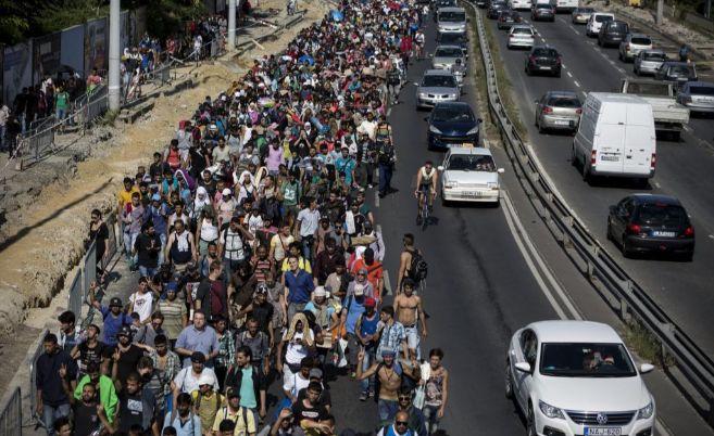 Miles de personas caminan por una carretera húngara rumbo a Austria.