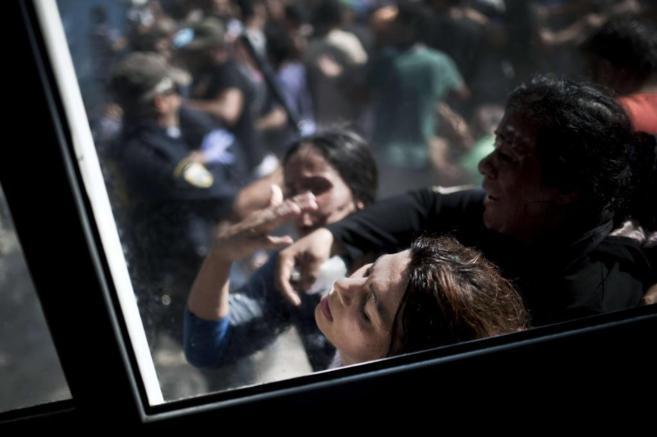 Una mujer se desmaya mientras la policía intenta dispersar una...