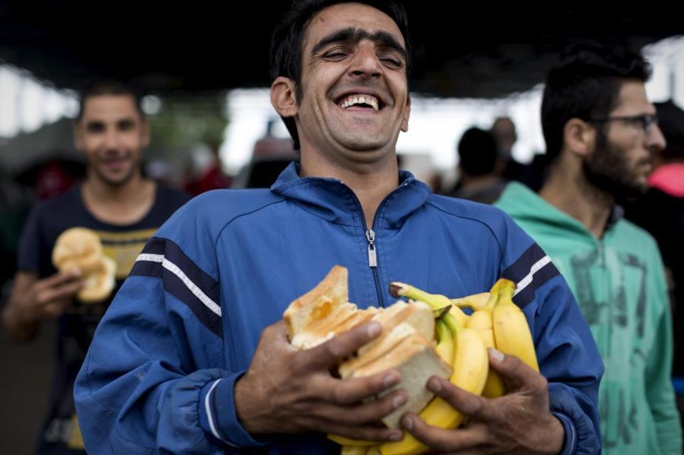 Los refugiados sonríen satisfechos tras ser atendidos y recibidos por...