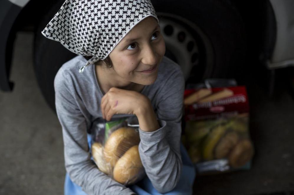 Una niña refugiada recibe pan nada más llegar a la frontera entre...