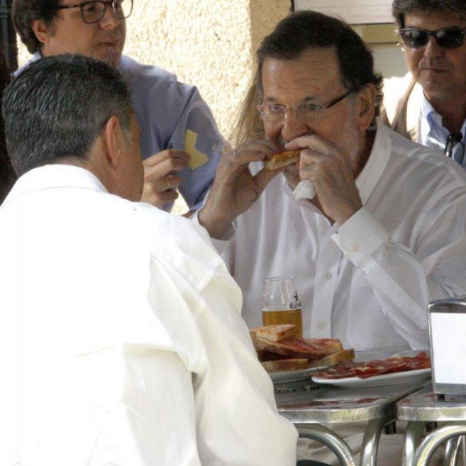 Rajoy disfruta de una tosta de pan con tomate, junto a García Albiol,...