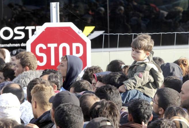 Un grupo de inmigrantes hace cola en la estación de tren en el paso...