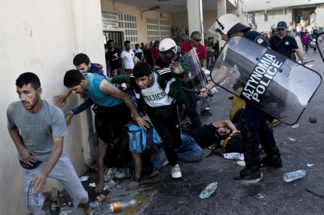 Policías golpean a migrantes durante las protestas de ayer en la isla...