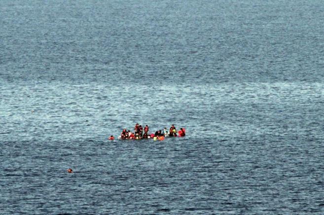 Un grupo de refugiados intenta mantenerse a flote en su bote cerca de...