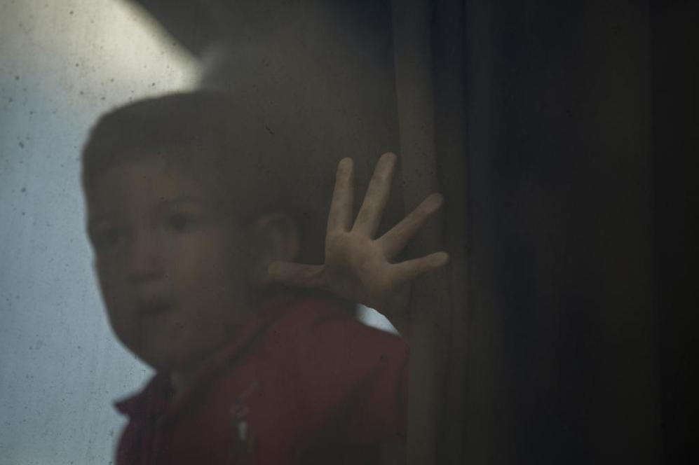 Un niño mira a través de la ventana de un autobús cargado de...