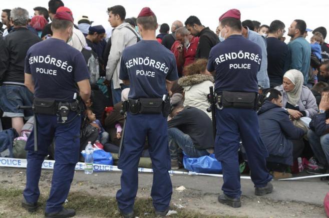 La Policía húngara vigila a un grupo de refugiados sirios, que...