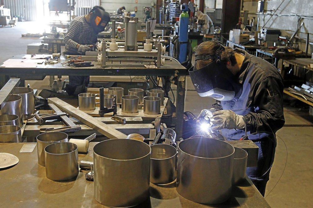 Dos operarios trabajan en el diseño de los recipientes para quesos.