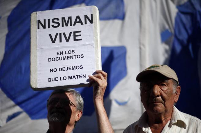 Un hombre sostiene una pancarta durante una protesta en el exterior...