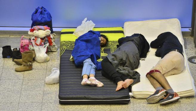 Una familia de refugiados descansa sobre dos colchones en un recinto...