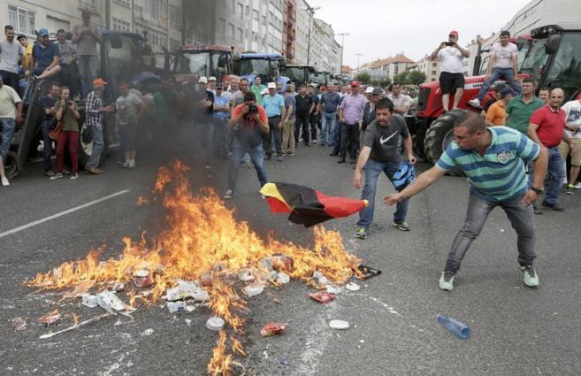 Centenares de ganaderos queman una bandera alemana y productos...